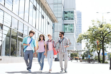 Full-length male and female friends walking on city street