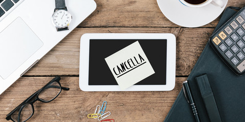 Cancella, Italian text for Cancel , yellow sticky note, office desk with computer technology, high angle