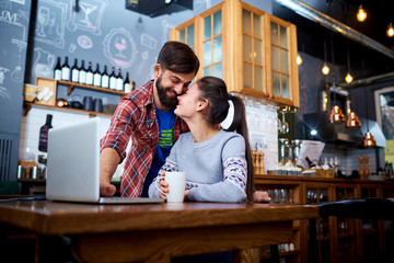 Young couple in a cafe restaurant with  laptop smiling at the table.