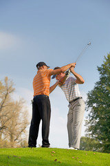 Golf professional helping young man with his swing