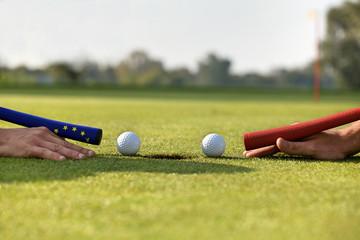 Human hands using golf balls to play pool