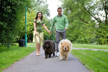 Young couple walking with pet dogs