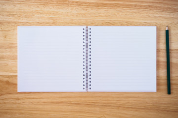 notebook top view with pencil on brown wood desk