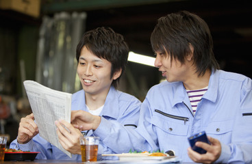 Two Male Workers Reading Newspaper at Lunch Break
