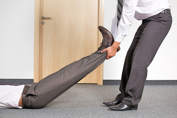 Businessmen pulling colleague's leg at office