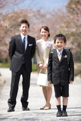 Elementary school boy with parents under cherry blossoms