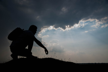Silhouette of man sitting and sky with sunlight