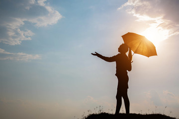 Silhouette woman hold umbrella and sky with sunlight