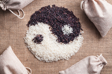 Ying and Yang symbol  spelled by black and white rice with burlap sack bag on canvas