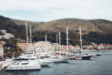 Tilt-shift image of boats moored at lake in town