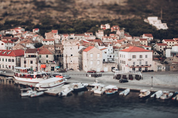 Tilt-shift image of boats moored at lake by houses in town