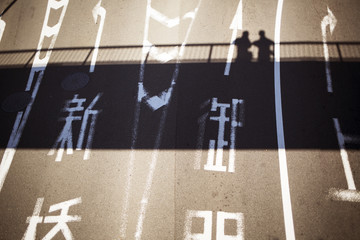High angle view of Japanese text on road with shadow of people on bridge