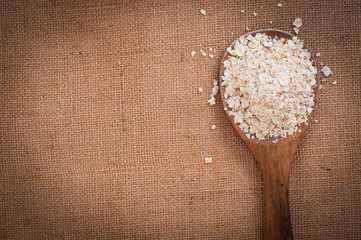 Wooden spoon with Oat flakes meal on burlap surface