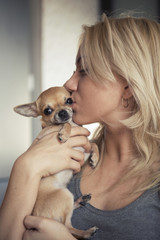 Close-up of teenage girl kissing Chihuahua at home