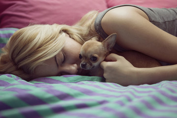 Teenage girl with Chihuahua lying on bed