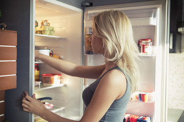 Teenage girl looking in refrigerator at kitchen