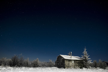House on snow covered field at night