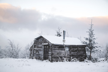 Snow covered house against cloudy sky