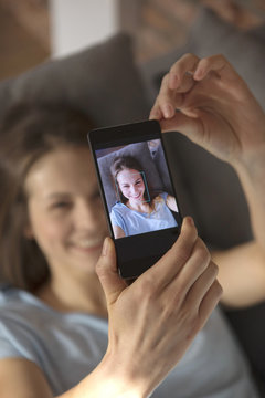 High angle view of woman clicking selfie on smart phone at home