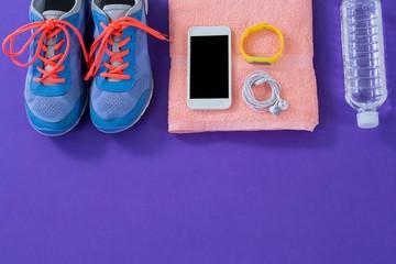 Sneakers, water , towel, phone with headphones