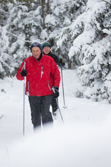 seniors in winter on snow with skis cross-country skiing