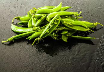 Fresh wet Peas on black darkboard surface with water drops