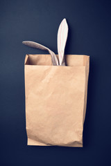 Easter bunny in a paper bag. Rabbit. Black background. Easter ideas. Easter eggs. Space for text. Image in trendy toning.