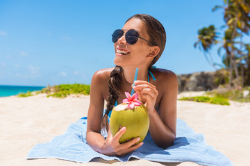 Sunglasses beach woman drinking coconut water having fun on summer vacation. Tropical travel holidays. Bikini casual girl relaxing lying down with natural healthy drink.