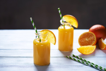 Fresh orange juice in the jar with straw on white wood table. Vertical shot