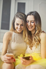 Smiling girls checking their smartphones