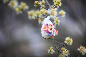 Decorative easter egg. An egg on a tree branch. Flowers blossom on the tree
