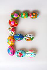 """One of the letters of the word """"Easter"""". Letters are made of Easter eggs, of different colors and with different patterns. On a white background"""