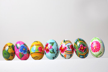 Easter eggs arranged in a row, on a white background