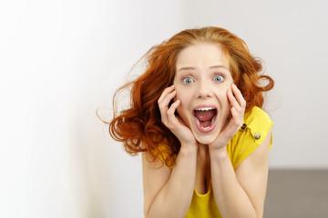 überraschte frau schreit vor freude und macht große augen