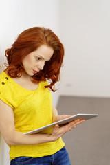 frau schaut mit ernstem gesichtsausdruck auf ein tablet-pc