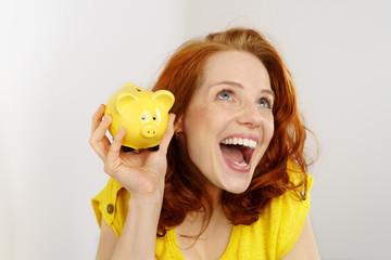 glückliche frau mit einem gelben sparschwein