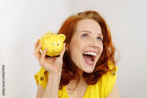965469042b glückliche frau mit einem gelben sparschwein