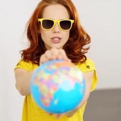 frau mit gelber sonnenbrille zeigt einen globus