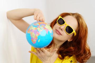 frau mit sonnenbrille zeigt einen globus