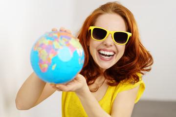 lachende frau mit sonnenbrille und globus