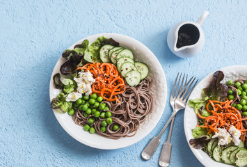 Soba noodles buddha bowl. Buckwheat  noodles with vegetables on a blue background, top view. Vegetarian healthy food concept