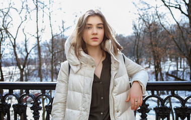 Beautiful young blonde woman standing on the spring city park in warm clothes. Cold season lifestyle freshness concept