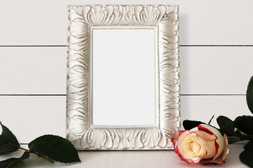Frame Mockup with empty place for text or picture. Shabby chic white colored interior, beautiful Rose.