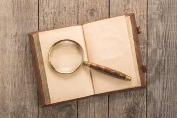 Old book with a magnifying glass on the table