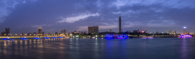 Panoramic view of Cairo city center at twilight, the Kasr El Nile Bridge and the island of Zamalek with its colorful boats on the Nile river. Papier Peint