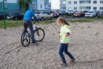 Children are playing in the yard, a boy is riding a bike, a girl is standing on the ground
