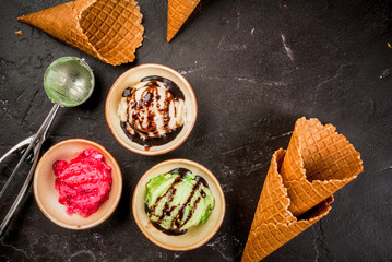 Selection of colorful homemade ice cream: lemon (pistachio) green, berry pink, white vanilla. With a spoon for serving balls, waffle cones, on a slate board, on a black table. Top view, copy space
