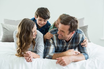 Family playing on bed in bedroom at home