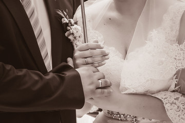 The groom holds the hand of a bride in a white dress with a bouquet