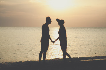 Loving couple on the beach. people stand at sunset in the shade.